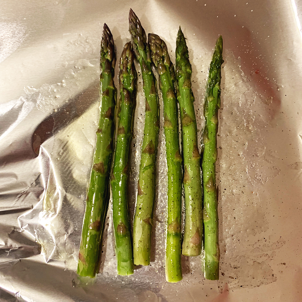 Asparagus, butter, salt and pepper on foil