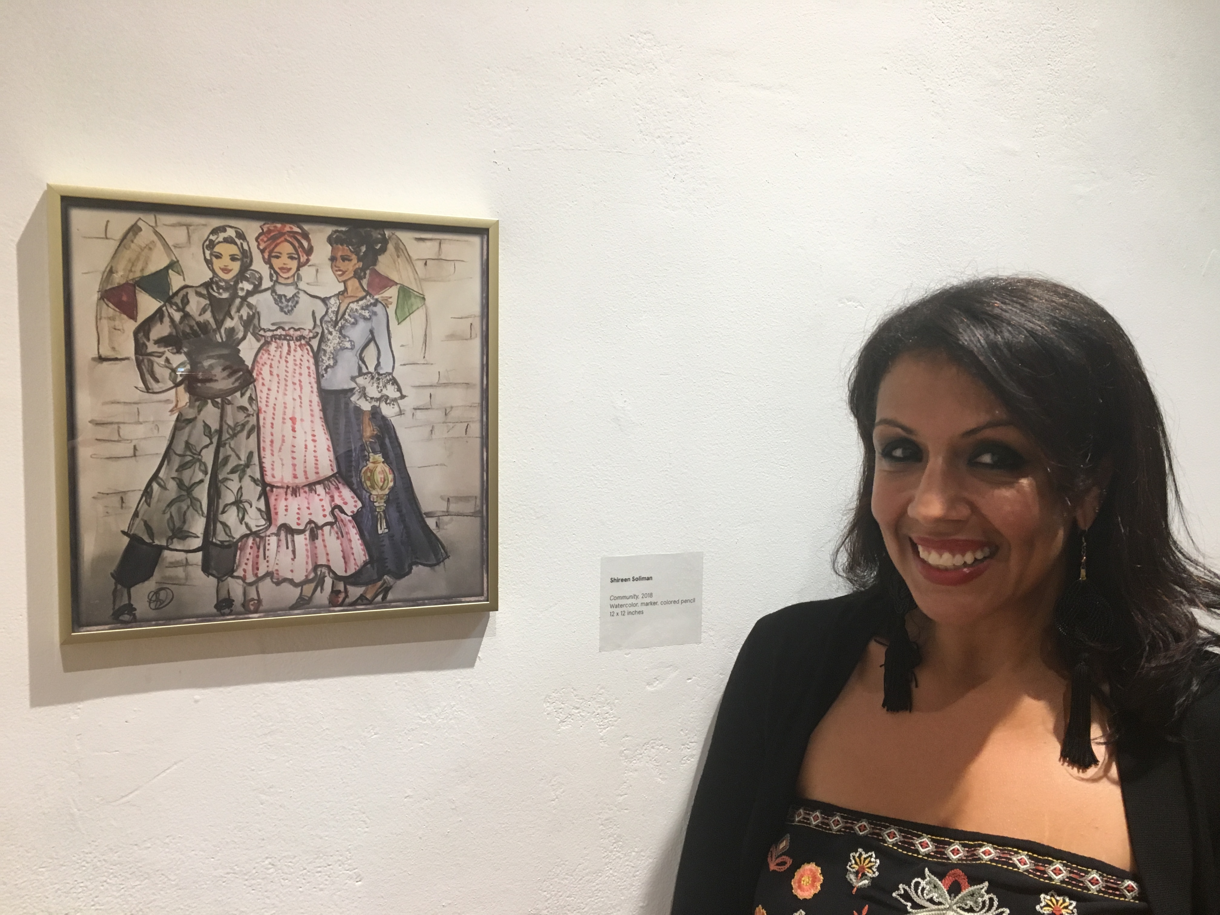Shireen standing with her art piece: Community