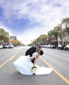 A bride and a groom sitting in the middle of the road