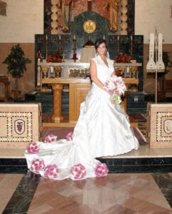 The bride standing near the altar and holding a bouquet