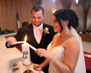 The bride and groom lighting a candle