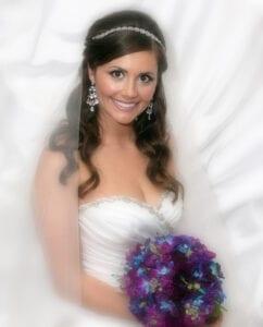 A bride holding a purple bouquet of flowers