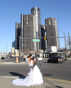 A bride and a groom kissing near an intersection