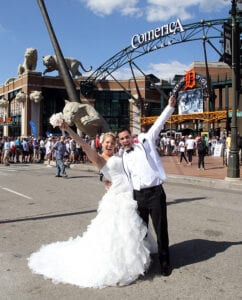 A bride and a groom posing in front of an amusement park