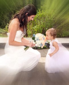 The bride and a little girl smelling her bouquet