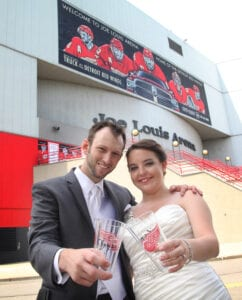 The bride and the groom holding a cup outside Joe Louis Arena