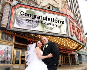 A bride and a groom outside a movie theater