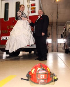 The bride on the firetruck and the groom holding her