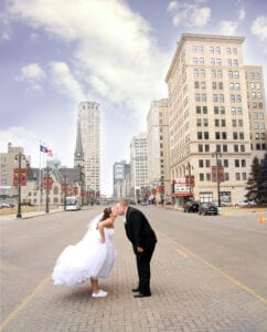 The bride and groom kissing on the streets