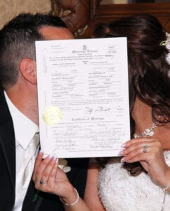 A bride and a groom kissing behind a marriage certificate