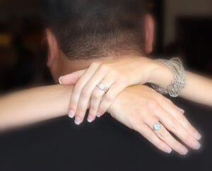 A woman's arms around a man, showing the ring on her hand