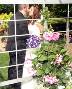 A bride and a groom kissing behind a net