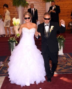 A bride and a groom wearing sunglasses
