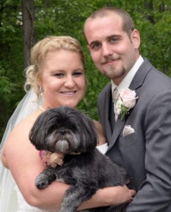 A bride and a groom holding a dog