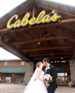 A bride and a groom kissing in front of Cabela's