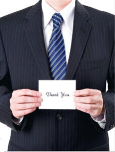 Man holding a thank you note, critical to landing a job