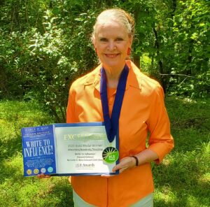 """Carla D. Bass, poses with her multiple award-winning book, Write to Influence!"""""""