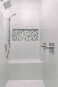 white tiled shower with mosaic