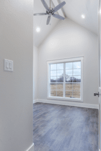 smooth floor with high ceiling, ceiling fan, and large window