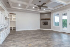 large room with fireplace, windows, and cabinets