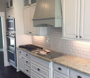 kitchen with hood range and two ovens