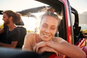 Millennial white couple on a road trip driving in open top car, women leaning on car door, close up