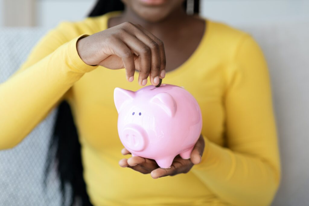 Money Savings. Closeup Of Black Woman Putting Coin To Piggy Bank