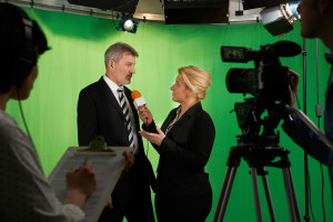 Female Presenter Interviewing In Television Studio With Crew In Foreground