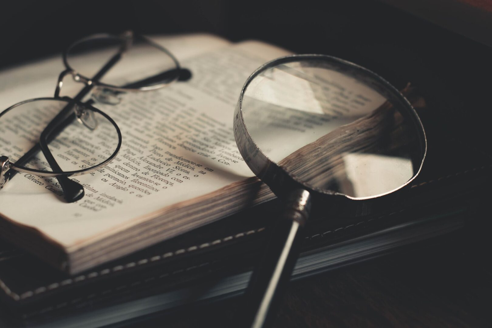 gray-magnifying-glass-and-eyeglasses-on-top-of-open-book-3109168 (1)