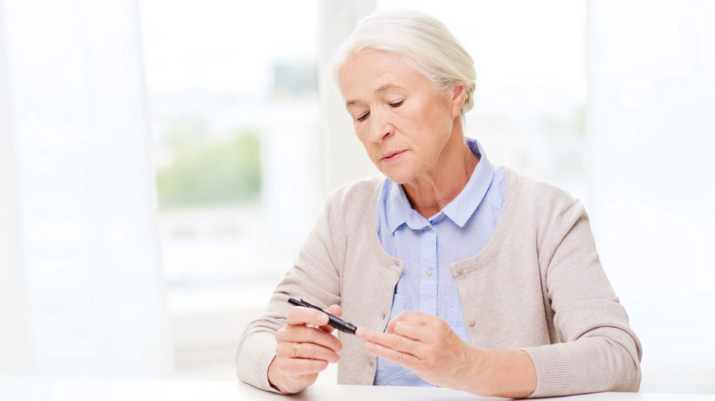 Woman testing finger for diabetes
