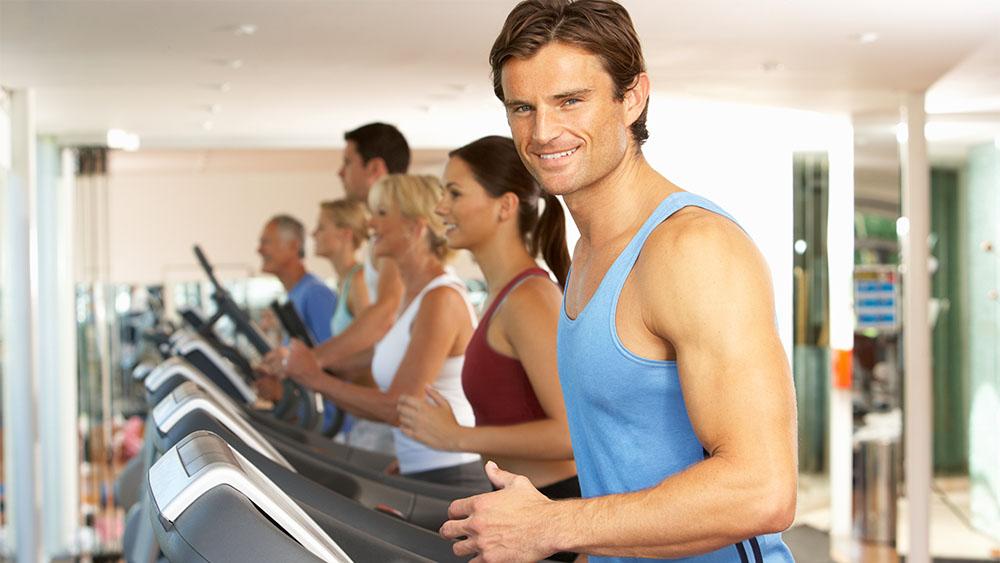 Smiling man running on treadmill