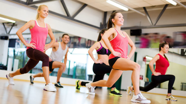 Individuals doing lunges on exercise floor
