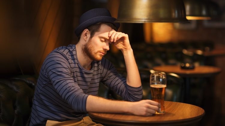 Lonely man sitting at bar table with drink