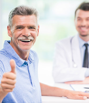 Man giving thumbs up with doctor