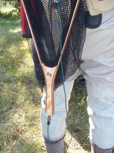 Trout Net - hanging from a magnetic release - Handle down - With green bungee lanyard.