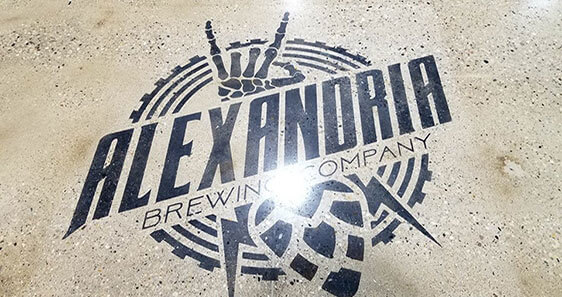 Alexandria Brewing Company's logo embedded in treated concrete on the floor of their brewery