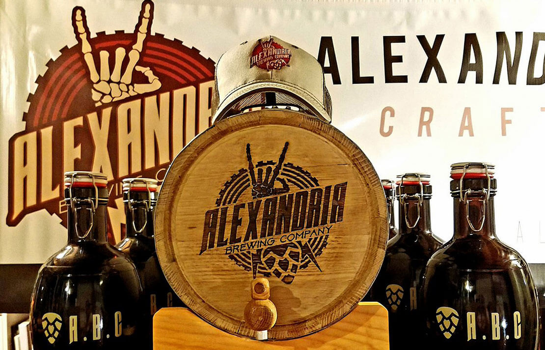 Alexandria Brewing Company's logo and alternate marks are showcased on a banner, hat, growlers, and barrel
