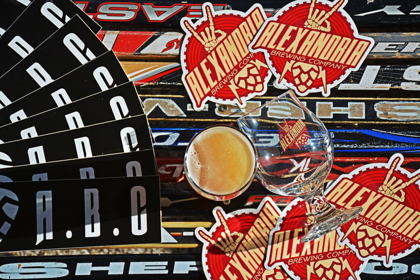 Several stickers featuring the Alexandria Brewing Company logo and alternate mark are displayed on a table