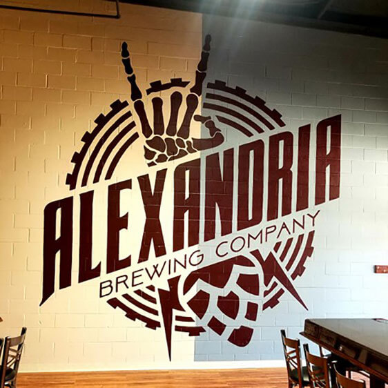 Giant mural of the Alexandria Brewing Company logo within their store