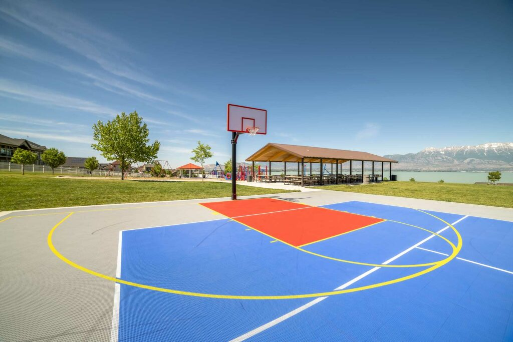 Photo of outdoor basketball court with playground in background