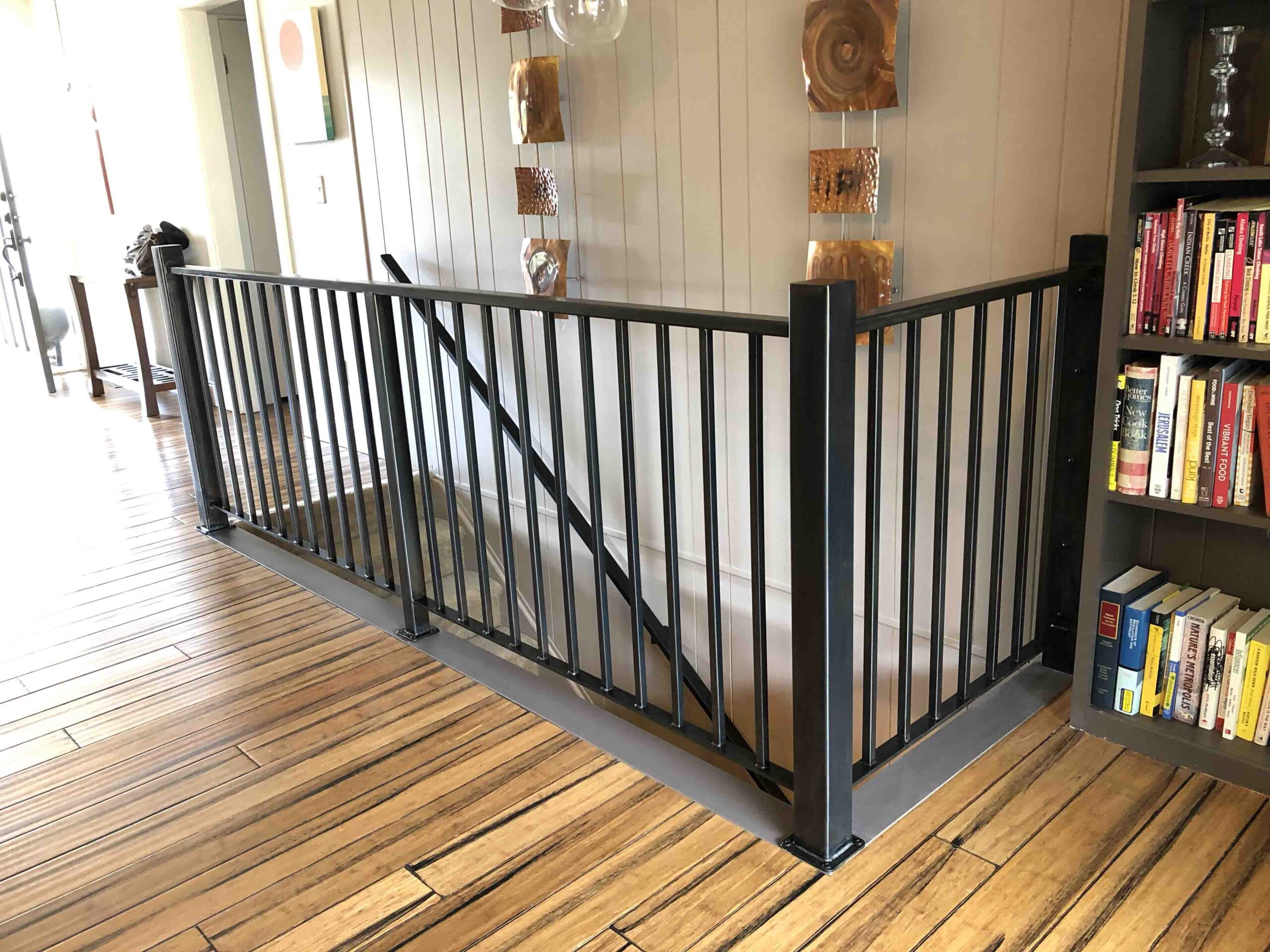 This 1960's ranch needed a new guardrail and handrail, and the design needed to complement the vertical wood paneling as well as the lines of the flooring. The patina softened the metal tone to accentuate other metallic features of the owner's possessions.