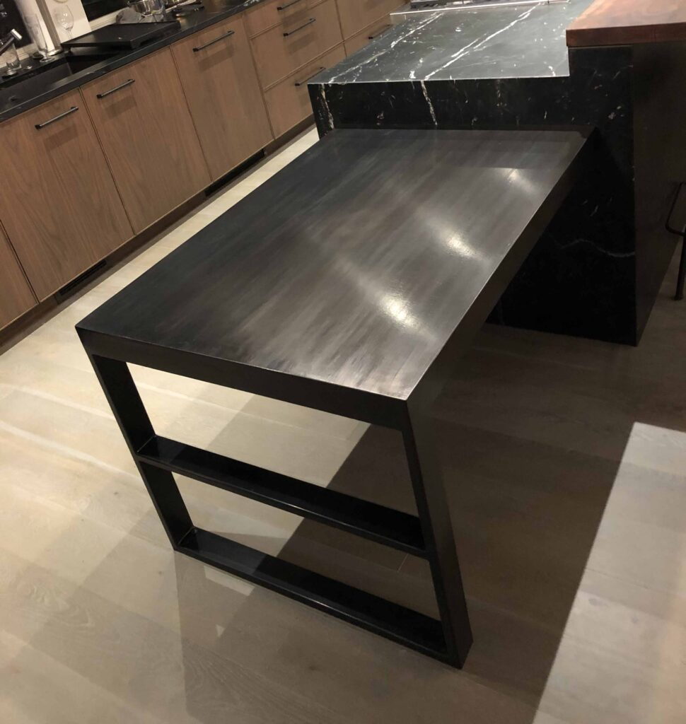 Mild Steel kitchen island table with hidden fasteners that lock it to the granite counter. Patina applied.