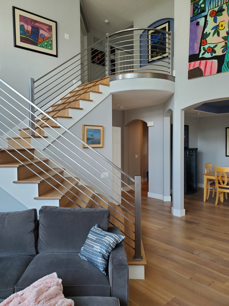 Modern railing for an impressive grand staircase draws the eye to the clean lines and brilliance of the raw metal.