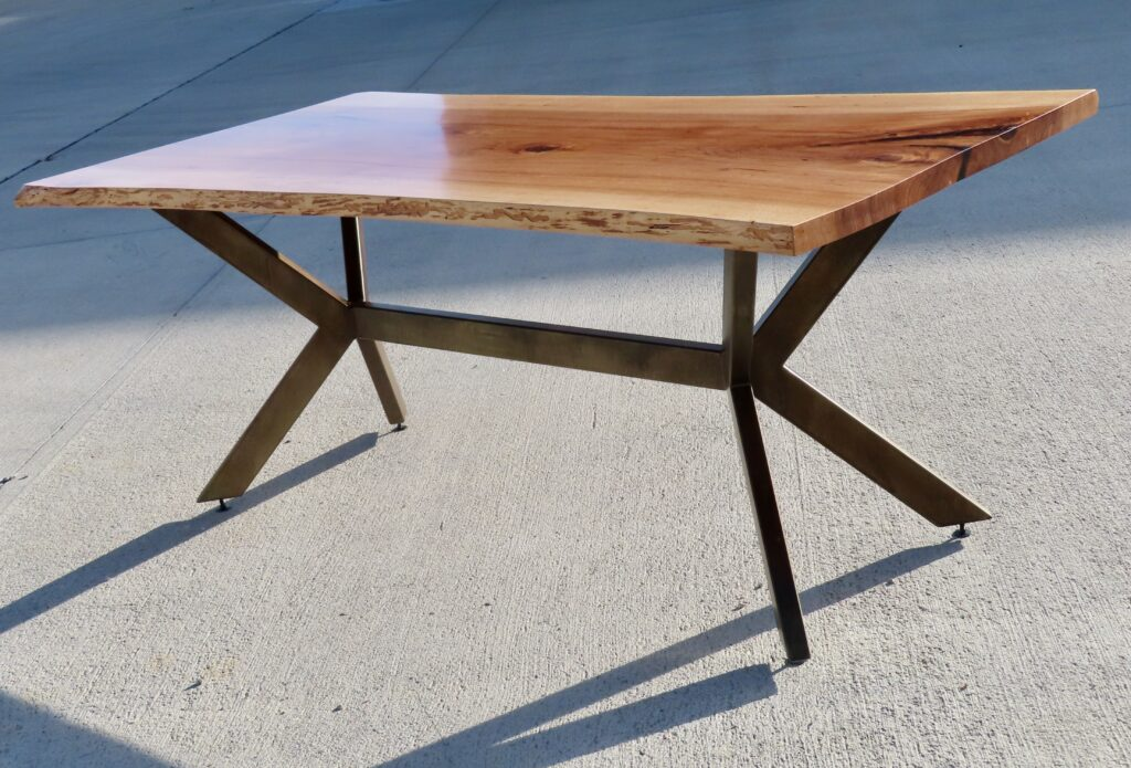 Live edge pecan slab sits comfortably on a trestle-inspired metal base.