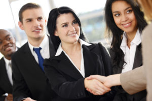 Five business people with two shaking hands in an office