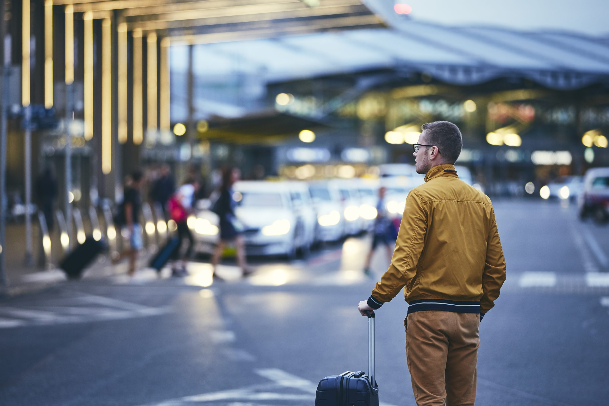 Passenger walking outside airport terminal. Rear view of young man with luggage at night.