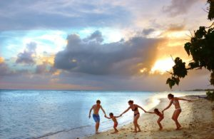 Family on a beach who needs travel insurance