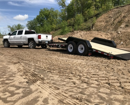 2020 TB Series Tilt Bed Trailer, tilted and pulled behind white Chevy pickup on the sand.