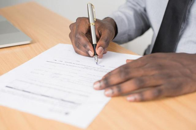 Photo of hands filling out a form.