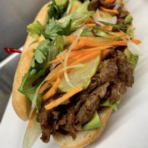 Philli Styl Banh Mi at Little Pub: Ginger soy marinated shaved steak on a grinder roll topped with pickled vegetables, sliced avocado, and sriracha aioli